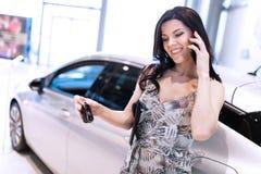 Teléfono de discurso de la morena admirable y el possing cerca de su nuevo coche en la sala de exposición de la representación fotos de archivo