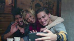 Teléfono de invitación video Amigos felices que usan el teléfono móvil en café metrajes