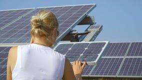 Teléfono de la charla de la mujer y batería solar chekcking almacen de metraje de vídeo