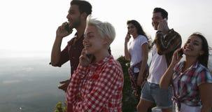 Teléfono de la gente que invita al top de la montaña, sonrisa feliz de discurso de la conversación telefónica del grupo de los tu almacen de video