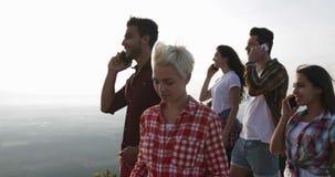 Teléfono de la gente que invita al top de la montaña, sonrisa feliz de discurso de la conversación telefónica del grupo de los tu almacen de metraje de vídeo