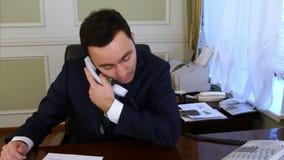 Teléfono de la línea horizonte del hombre de negocios que habla hermoso que comprueba al equipo almacen de metraje de vídeo