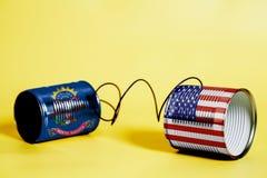 Teléfono de la lata con los E.E.U.U. y las banderas del estado de Dakota del Norte Concepto de la comunicación imagen de archivo libre de regalías