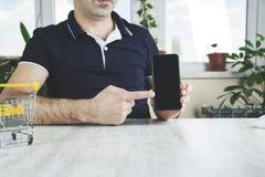 Teléfono de la mano del hombre con la cesta imagen de archivo libre de regalías