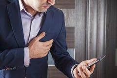 Teléfono de la mano del hombre con en el corazón fotos de archivo
