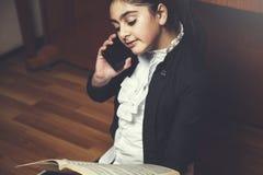 Teléfono de la mano de la muchacha con el libro de música foto de archivo