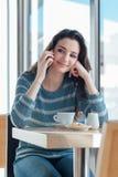 Teléfono de la muchacha que llama en el café Imagen de archivo libre de regalías