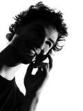 Teléfono de la silueta del hombre joven Foto de archivo