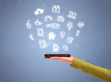 Teléfono de la tableta de la tenencia de la mano con los iconos exhaustos Imagen de archivo libre de regalías