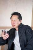 Teléfono de mediana edad del hombre Imagen de archivo libre de regalías