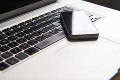 Teléfono de Movil en un ordenador portátil Imagen de archivo libre de regalías