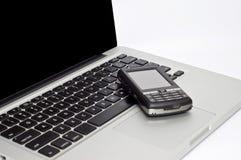 Teléfono de PDA en la computadora portátil Fotografía de archivo