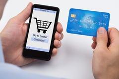 Teléfono de Person Shopping Online On Mobile Imagen de archivo libre de regalías