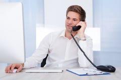 Teléfono de Sitting In Front Of Computer Talking On del hombre de negocios Imagenes de archivo