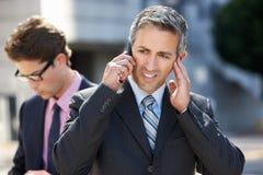 Teléfono de Speaking On Mobile del hombre de negocios en alrededores ruidosos Imagenes de archivo