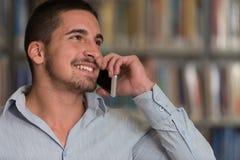 Teléfono de Talking On The del estudiante masculino en biblioteca Imágenes de archivo libres de regalías