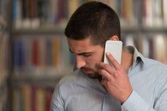 Teléfono de Talking On The del estudiante masculino en biblioteca Fotos de archivo libres de regalías