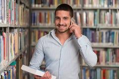 Teléfono de Talking On The del estudiante masculino en biblioteca Imagenes de archivo