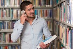 Teléfono de Talking On The del estudiante masculino en biblioteca Fotografía de archivo libre de regalías