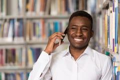 Teléfono de Talking On The del estudiante masculino en biblioteca Imagen de archivo libre de regalías