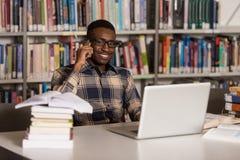 Teléfono de Talking On The del estudiante masculino en biblioteca Foto de archivo libre de regalías