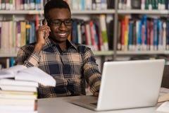 Teléfono de Talking On The del estudiante masculino en biblioteca Imagen de archivo