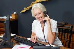Teléfono de Using Computer And del recepcionista del hotel Foto de archivo