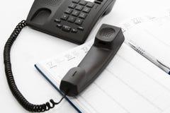 Teléfono del arreglo en agenda y pluma Imágenes de archivo libres de regalías