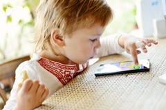 Teléfono del juego de la muchacha en café Foto de archivo libre de regalías