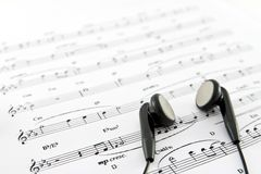 Teléfono del oído en la tapa de una hoja de música Foto de archivo