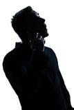 Teléfono del retrato del hombre de la silueta sorprendido Imagen de archivo libre de regalías