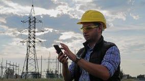 Teléfono del uso de la electricidad del ingeniero durante puesta del sol almacen de video
