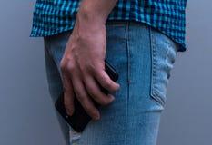 Teléfono a disposición bajado El hombre en vaqueros y una camisa de tela escocesa Imagen de archivo libre de regalías