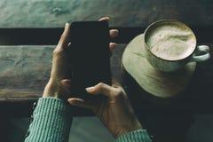 Teléfono a disposición y una taza de café en la tabla foto de archivo