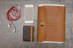 Teléfono elegante, cartera, auriculares y un cuaderno de cuero en un blac fotos de archivo
