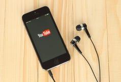 Teléfono elegante con el logotipo de YouTube en su pantalla y auriculares Imagen de archivo libre de regalías