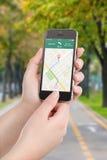 Teléfono elegante con el uso de la navegación de los gps del mapa en la pantalla Foto de archivo libre de regalías