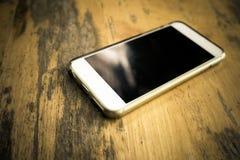 Teléfono elegante con la pantalla en blanco que miente en la tabla Foto de archivo libre de regalías