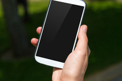 Teléfono elegante con la pantalla negra en fondo natural Fotos de archivo