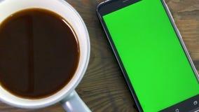 Teléfono elegante con la pantalla verde al lado de la taza de café almacen de metraje de vídeo