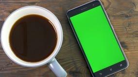 Teléfono elegante con la pantalla verde al lado de la taza de café metrajes