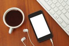 Teléfono elegante con la taza de los auriculares, del teclado y de café Fotografía de archivo libre de regalías