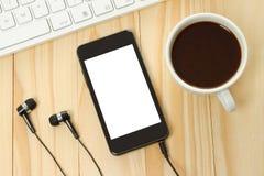 Teléfono elegante con la taza de los auriculares, del teclado y de café Fotos de archivo libres de regalías