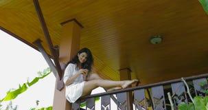 Teléfono elegante de la célula del uso de la mujer joven que se sienta en la sonrisa feliz del balcón, charla hermosa de la mucha almacen de video