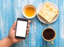 Teléfono elegante de la exhibición blanca a disposición, tostada, miel, taza de café Imágenes de archivo libres de regalías