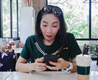 Teléfono elegante de las mujeres chocado en la cafetería Imagen de archivo libre de regalías