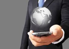 Teléfono elegante del control del hombre de negocios con el globo digital que brilla intensamente Imagen de archivo