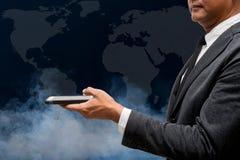 Teléfono elegante del control del hombre de negocios con el mapa del wolrd Fotos de archivo