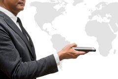 Teléfono elegante del control del hombre de negocios con el mapa del wolrd Foto de archivo