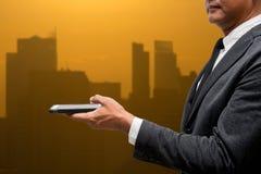 Teléfono elegante del control del hombre de negocios con la luz de la ciudad en fondo Fotografía de archivo